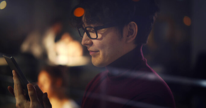 Asian office worker using smartphone standing near window in office late at night.