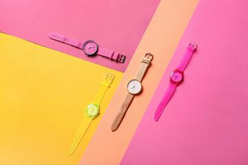 Stylish wrist watches on colorful background