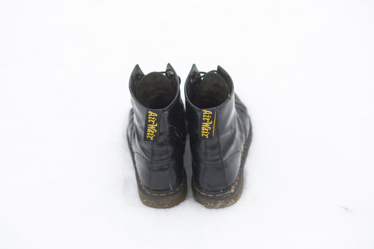 Black strong Dr Marten boots in snow on a  winter's day.