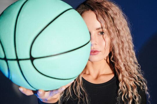 young beautiful woman holding a basketball ball.