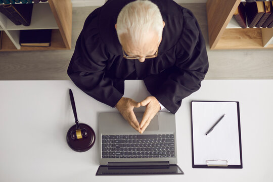 Concept of providing law consultation and legal advice online. Trustworthy wise senior judge, attorney or lawyer sitting at office desk with laptop computer, papers and gavel. High angle, from above