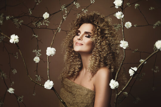 Lovely young woman with Afro hairstyle and beautiful make-up with a lot of white flowers