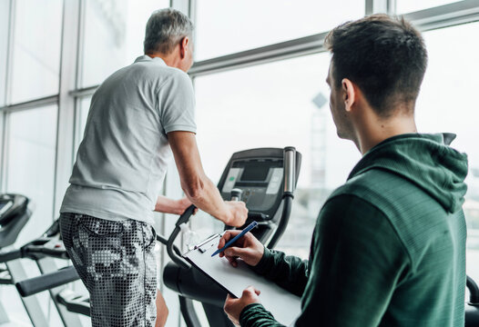 The focus is on a training plan held by a male coach. The photo shows two men in the gym, one of them performing an exercise on a simulator, the other watching