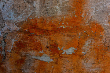 Wall surface with old plaster and traces of new orange paint.