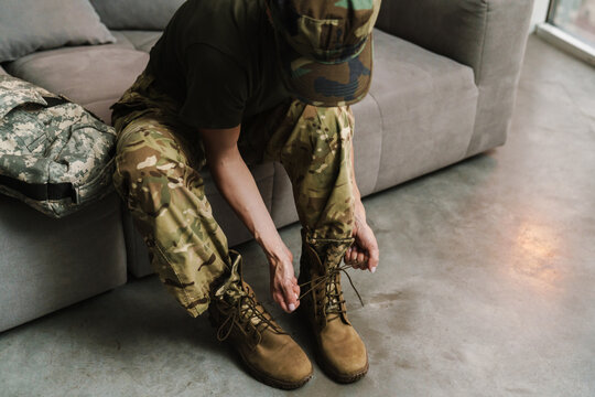 Soldier woman tying her shoe laces while sitting on couch indoors