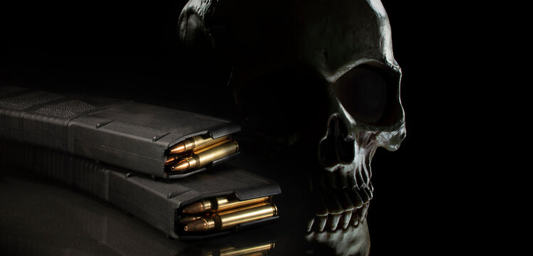 Human skull on a dark background with loaded thirty round magazines for an AR-15