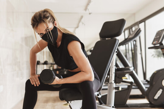 Young athletic woman wearing a prevention face mask during her fitness workout.