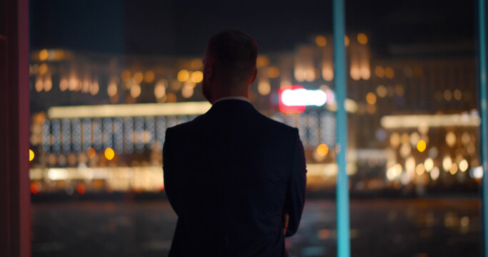 Back view of successful young businessman in suit is looking out of panoramic window.