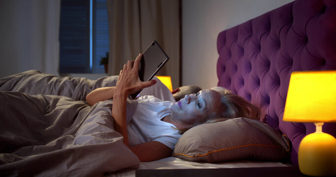 Sleepless senior woman in bed at night using mobile phone while husband sleeping