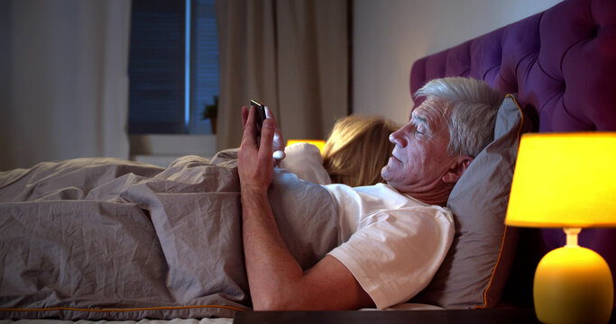 Senior man surfing internet on smartphone while his wife sleeping