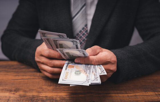 Business executive in formal suit Counting money that is bribe In order to offer or receive Bribe money to bad business people, ideas of giving and receiving bribes and corruption.