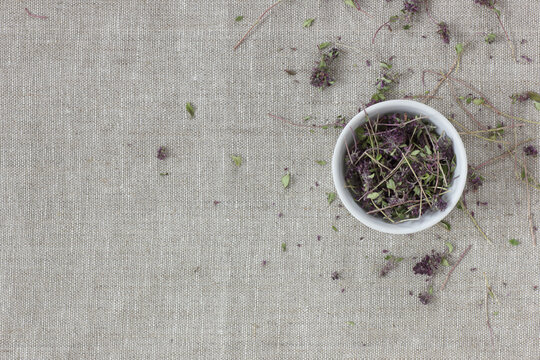 Thyme dried flower tea in a white bowl on linen textile with blossoms and buds nearby, closeup, copy space, flat lay, from above overhead top view, healthy herbal teas and natural supplement concept