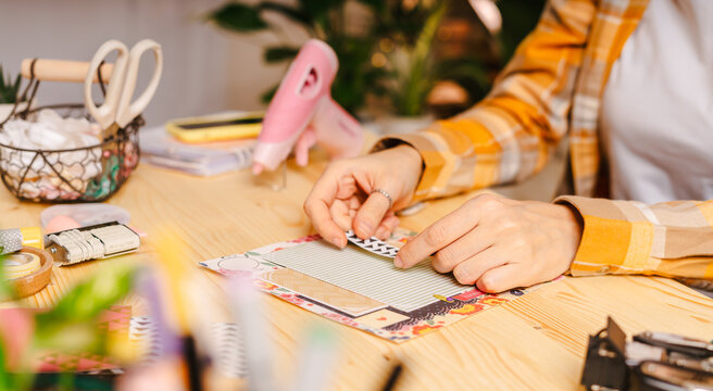 Cropped shot of women making homemade scrapbooking album from paper. DIY, hobby concept, gift idea, decor with handcraft attributes, home production, the process of creation, creativity.