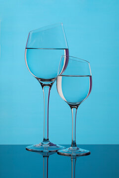 Two beveled glass goblets on a blue background