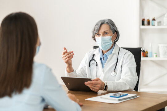 Senior mature female doctor in a lab coat and a face mask sitting at the desk,holding a pad,looking at the young lady patient, explaining medical results, digitized medical records in pandemic concept
