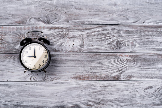 alarm clock showing five o'clock on wooden background