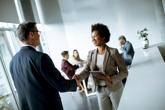Businesswoman holding digital tablet and looking at handsome colleague while shaking hands in office