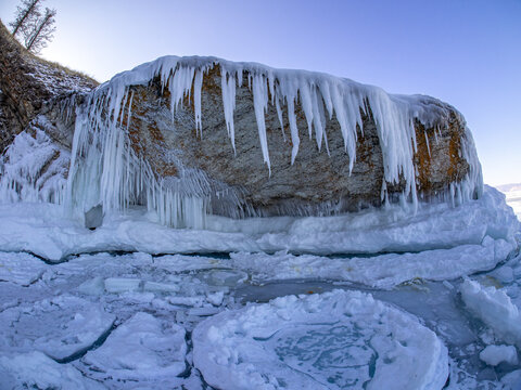 Long icicles hangs down under huge flat stone over frozen ice surface of the Baikal lake near frozen stony shore with snow in Siberia, Russia. Frozen winter landscape.