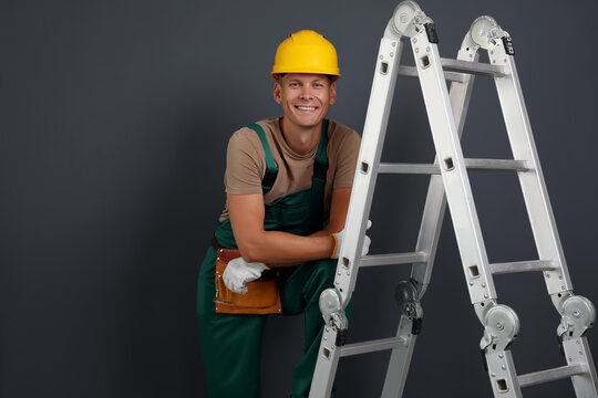 Professional constructor near ladder on black background
