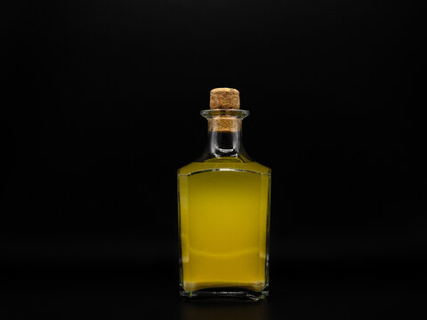 Glass bottle with alcohol drink closed with cork cap isolated on a black background. Transparent square bottle with yellow liquid. Front view of the vertical staying jar.