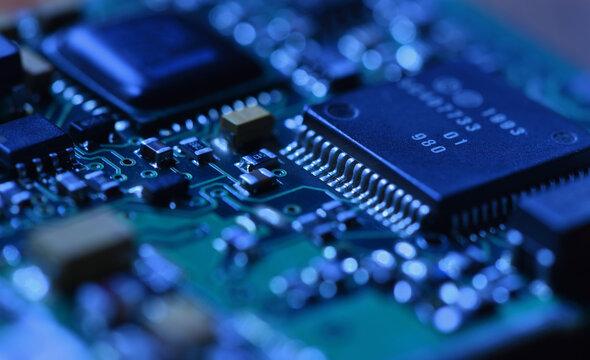 Digital microchip under dramatic blue light close-up