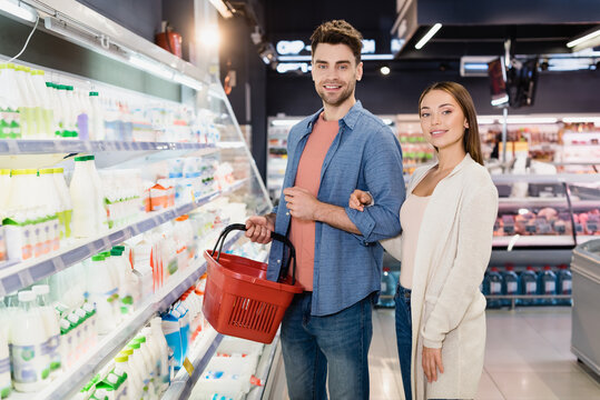 Smiling couple with shopping basket standing near food in supermarket