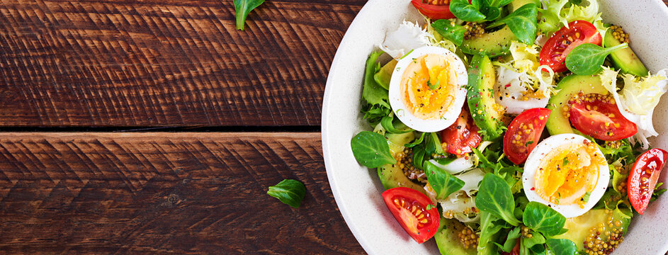 Fresh avocado salad with tomato, avocado, boiled eggs and fresh lettuce. Ketogenic diet breakfast.  Keto, paleo salad. Top view, banner, above