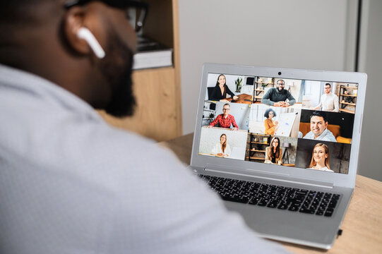 Close-up of African American man using app for distance video communication with coworkers, friends, webinar participants, meeting online in pandemic, looking at the laptop screen with people profiles