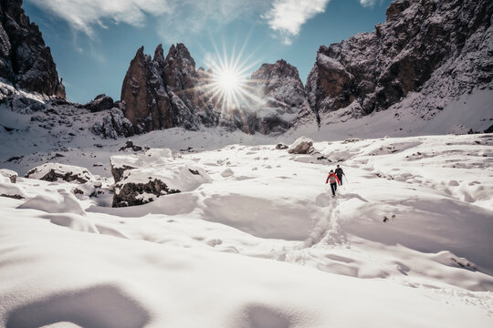 Two alpinists descending on snowy trail against sun rays in Dolomites