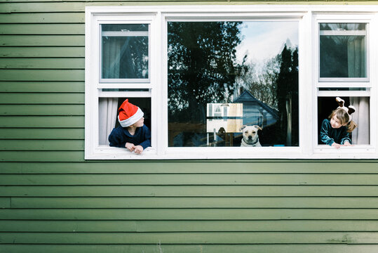 Two children and their dog looking out window waiting for Santa clause