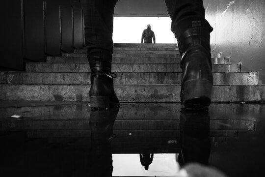 Silhouette of a man between women boots