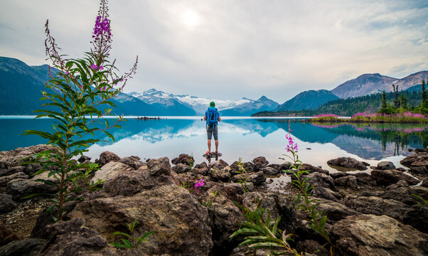 Male hiker standing on a rock overlooking a lake and snowy mountains