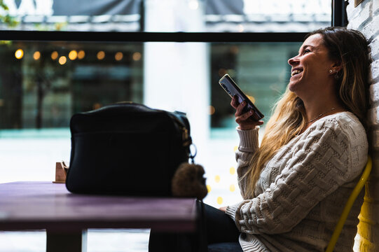 smiling woman in a coffee shop talking to her mobile phone