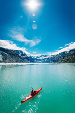 Woman kayaking in Glacier Bay National Park with glacier in background
