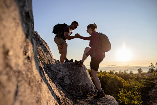 Two hikers help each other up mountain on Appalachian Trail in Maine