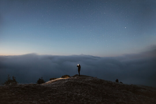Person Standing on the Mountain Above the Clouds During the Night