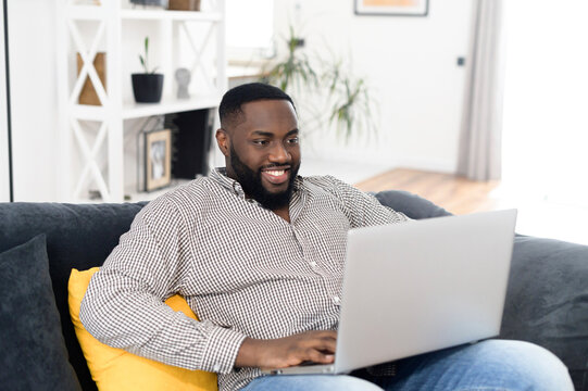 Portrait of smiling young African American guy placed the laptop on knees while relaxing on the sofa, typing email, messaging friend, freelancer working from home on a project, chatting, dating online