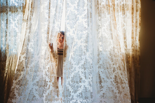 Little girl playing hide and seek with big vintage curtains at home