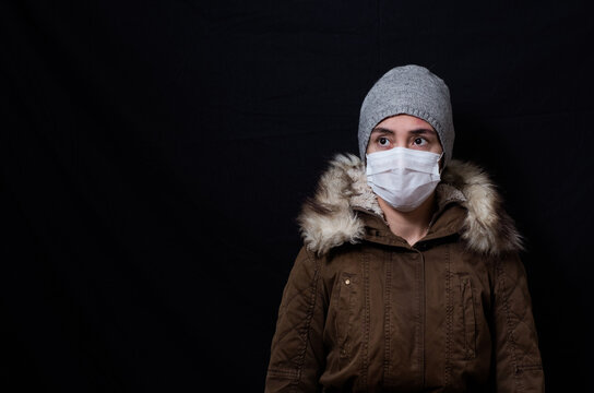 Woman in coat and mask looking worried