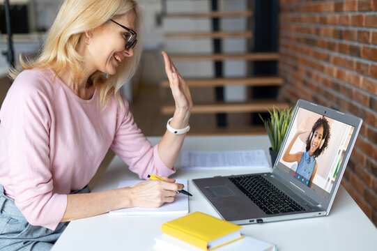 Online teacher, mentor conducts webinar, video lesson. Middle-aged female tutor greeting with a school-age African girl on the laptop screen. E-study concept