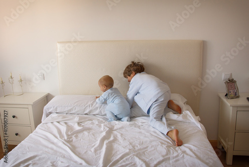 Brothers Playing On The Bed In Pajamas. Family Lifestyle