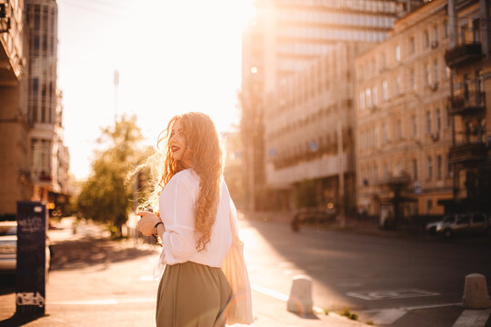 Happy young woman standing on street in city during summer