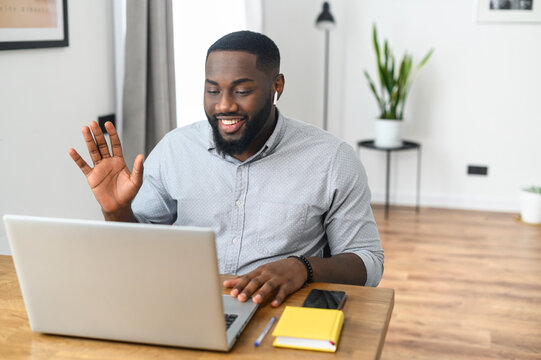 Smiling African American guy wearing airpods speaking close up, using laptop, looking at screen, greeting on video conference, holding a business call working from home. Head shot on light background