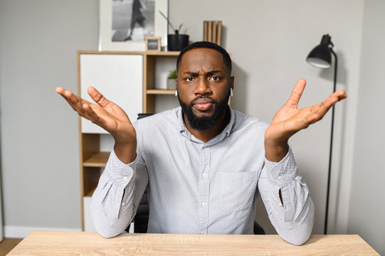 Mad and disappointed young African-American business owner is sitting at the desk and raising his hands up, feeling frustrated, demotivated from accrued issues, upset to hear the unexpected bad news