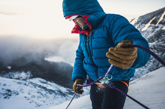 Male climber belays his lead climber during a cold winter alpine climb