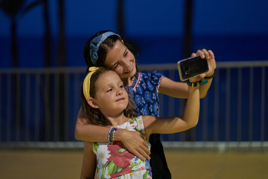 Portrait of two doughters wearing blue and white dresses and taking a selfie with their smartphone at night with a beach in the background. Vacation concept