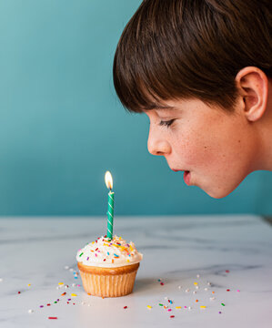 Young boy blowing out a candle on cupcake with frosting and sprinkles.