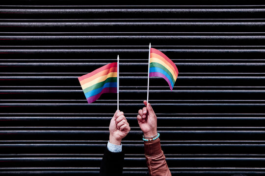 two hands holding pride flags. black background