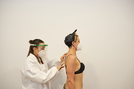 Physiotherapist working with patient in clinic. They wear masks to prevent the spread of corona virus