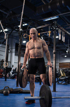 Strong elderly athlete with barbell weight plates